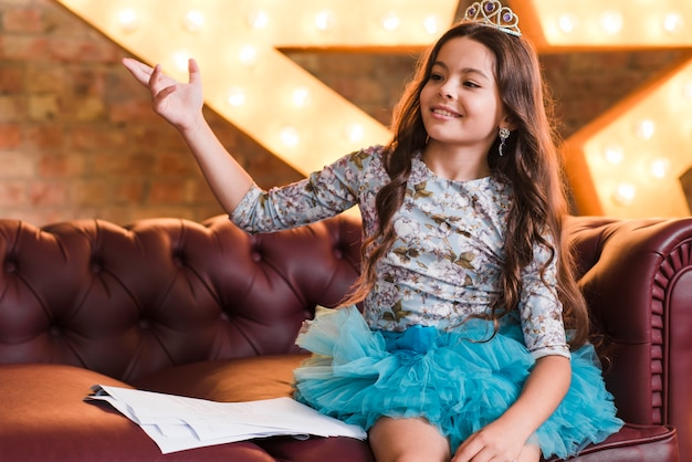 Uśmiechnięta dziewczyna jest ubranym korony obsiadanie na kanapie z scenariuszami