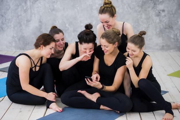 Uśmiechnięta dziewczyna jogin ćwiczeń, po przerwie w klasie, grupa przyjaciół ogląda przez telefon