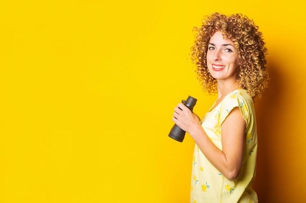 Uśmiechnięta dziewczyna kręcone trzymając lornetkę w dłoniach na żółtej powierzchni