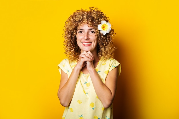 Uśmiechnięta dziewczyna kręcone z kwiatem we włosach na żółtym tle.