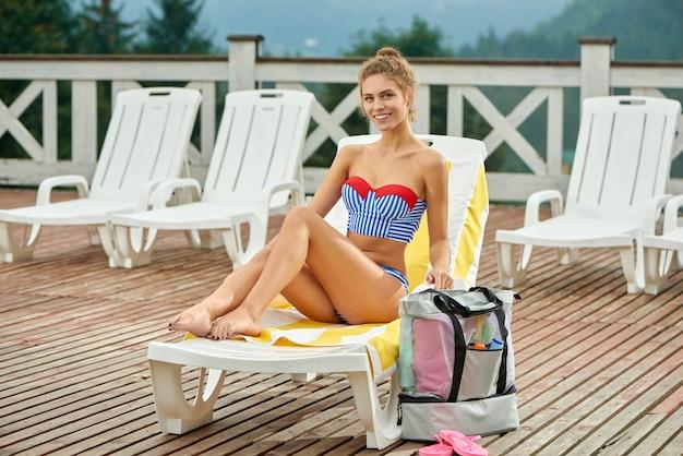 Uśmiechnięta dziewczyna, leżąc na leżaku w pobliżu basenu i opalając się.