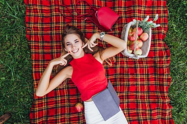 Uśmiechnięta dziewczyna leżąca w parku z książką i koszem owoców