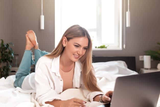 Uśmiechnięta dziewczyna leży na łóżku w sypialni i używa laptopa do pracy zdalnej