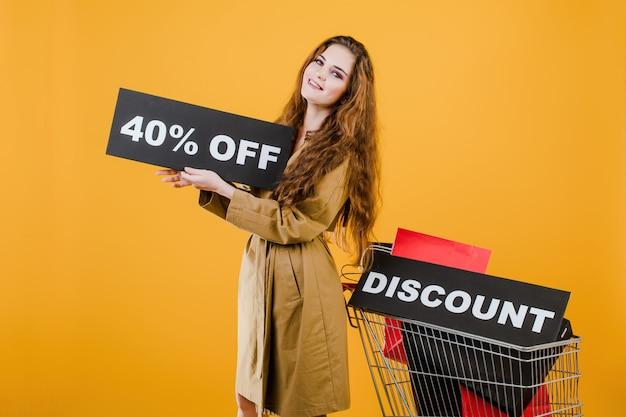 Uśmiechnięta dziewczyna ma zniżkę 40% zniżki na znak z koszykiem pełnym toreb na zakupy izolowanych na żółtym