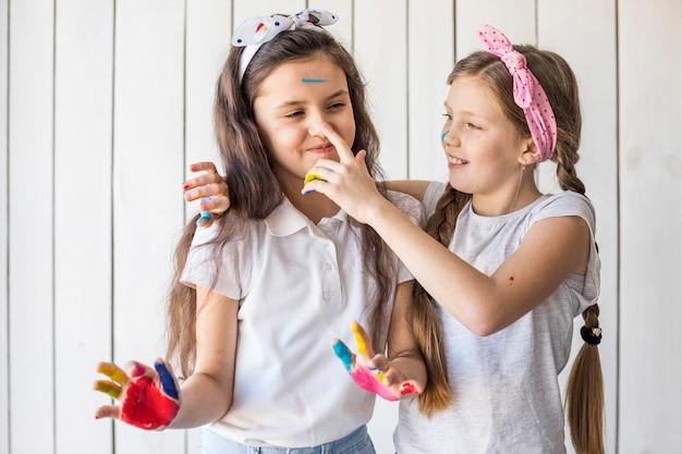 Uśmiechnięta dziewczyna maluje jej przyjaciela nos z kolor pozycją przeciw drewnianej ścianie