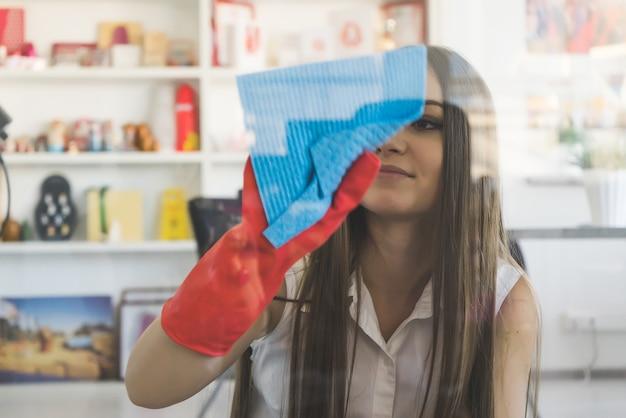 Uśmiechnięta dziewczyna myje okno niebieską szmatką