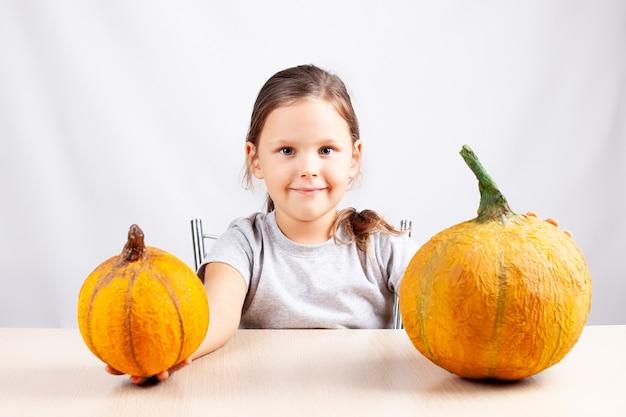 Uśmiechnięta dziewczyna na białej ścianie trzyma domowe dynie z papier-mache na halloween
