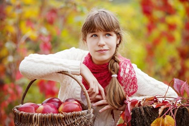 Uśmiechnięta dziewczyna nastolatka trzyma kosz jabłek w jesiennym ogrodzie. maluch jedzenie owoców na jesienne zbiory. zabawa na świeżym powietrzu dla dzieci. zdrowe odżywianie
