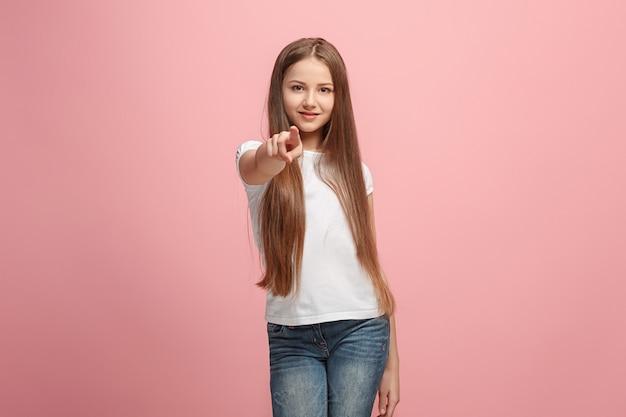 Uśmiechnięta dziewczyna nastolatka wskazując na aparat, portret zbliżenie w połowie długości na tle różowego studia.