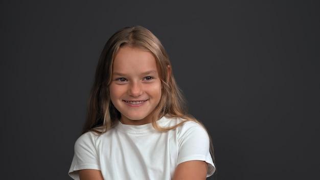 Uśmiechnięta dziewczyna nastolatka wyraża radość odwracając. mała blondynka kaukaski uśmiecha się z szelkami