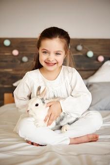 Uśmiechnięta dziewczyna obejmująca swojego królika w łóżku