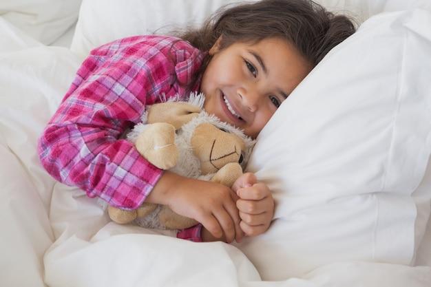 Uśmiechnięta dziewczyna odpoczywa w łóżku z faszerującą zabawką