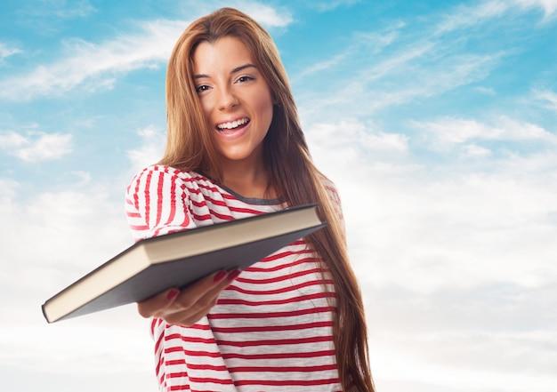 Uśmiechnięta dziewczyna oferuje książki na aparat fotograficzny