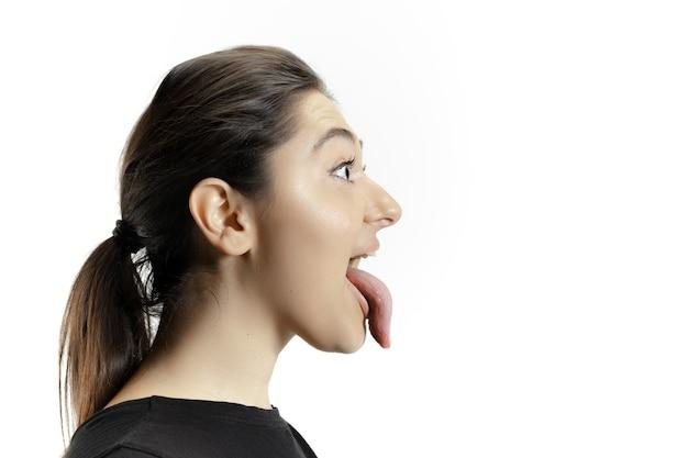 Uśmiechnięta dziewczyna otwiera usta i pokazuje długi wielki olbrzym na białym tle na białej ścianie. wygląda na zszokowanego, zafascynowanego, zdziwionego i zdziwionego. miejsce na reklamę. ludzkie emocje, marketing.