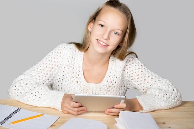 Uśmiechnięta dziewczyna patrząc na tablecie
