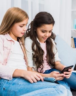 Uśmiechnięta dziewczyna patrzeje jej przyjaciela używa telefon komórkowego