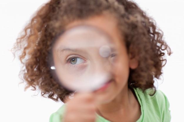 Uśmiechnięta dziewczyna patrzeje przez powiększać - szkło