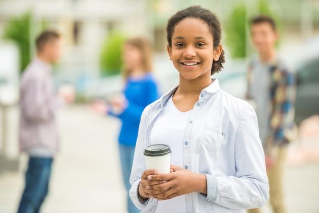 Uśmiechnięta dziewczyna pije kawę z jej przyjaciółmi przy parkiem.