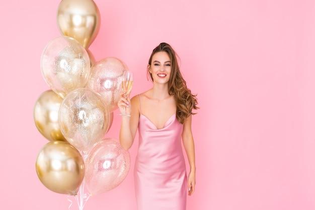 Uśmiechnięta dziewczyna podnosi kieliszek szampana, podczas gdy stoisko w pobliżu balonów przybyło na imprezę