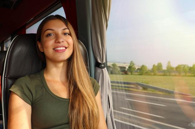 Uśmiechnięta dziewczyna podróżująca autobusem z drogą przez okno, patrząc w kamerę