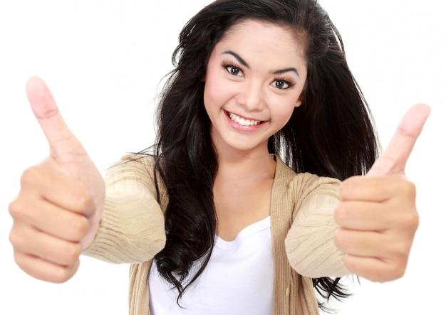 Uśmiechnięta dziewczyna pokazuje dwa aprobaty