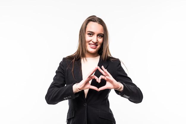 Uśmiechnięta dziewczyna pokazuje znak serca na białym tle nad białym