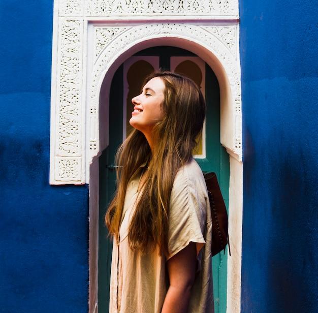 Uśmiechnięta dziewczyna przed łukowatym drzwiowym bocznym widokiem