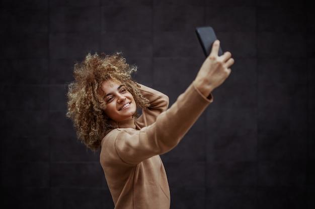 Uśmiechnięta dziewczyna pułapka za pomocą telefonu do zrobienia selfie.