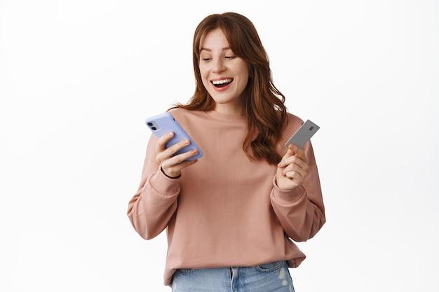 Uśmiechnięta dziewczyna robi zakupy online, trzymając kartę kredytową i telefon komórkowy, patrząc na ekran smartfona ze szczęśliwą twarzą, zamawiając coś w internecie, stojąc na białym