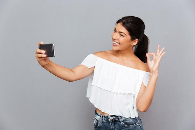 Uśmiechnięta dziewczyna robi zdjęcie selfie na smartfonie i pokazuje dobry gest na szarej ścianie