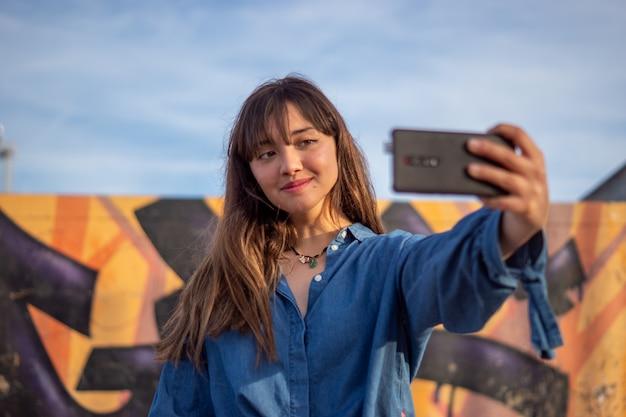 Uśmiechnięta dziewczyna robienia selfie w skateparku pod słońcem i pochmurnym niebem