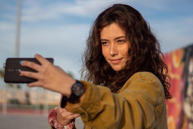 Uśmiechnięta dziewczyna robienia selfie w skateparku podczas złotej godziny