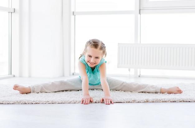 Uśmiechnięta dziewczyna rozciąga w domu
