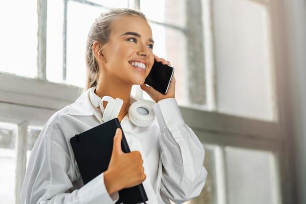 Uśmiechnięta dziewczyna rozmawia na smartfonie, trzymając czarny notatnik.