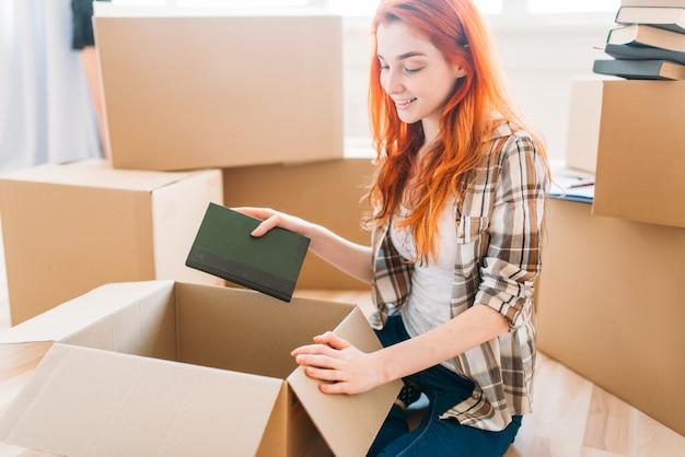Uśmiechnięta dziewczyna rozpakowywanie kartonów z książkami, nowy dom, parapetówka.