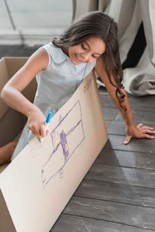Uśmiechnięta dziewczyna rysunek na kartonie markerem długopisy