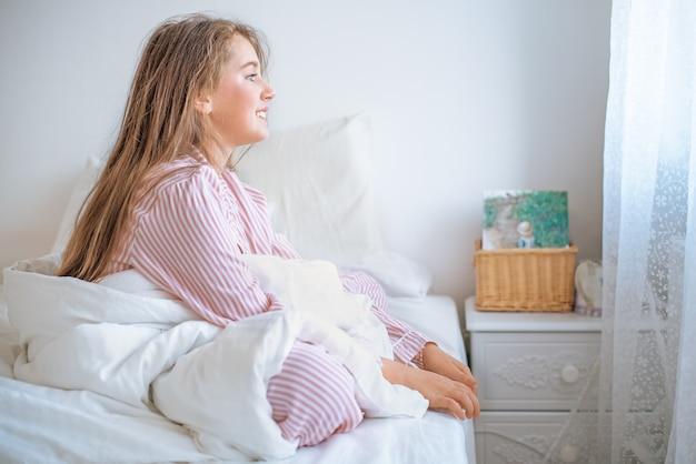 Uśmiechnięta dziewczyna siedzi na łóżku rano