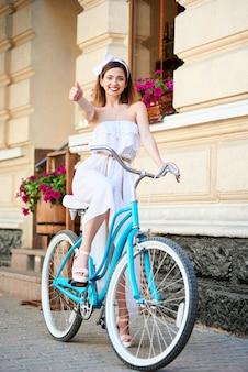 Uśmiechnięta dziewczyna siedzi na niebieskim rowerze retro i pokazuje palcem znak klasy, dobrze w starym mieście na tle kwiatów na ścianie