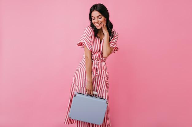 Uśmiechnięta dziewczyna skromnie spogląda w dół, pozując z mini walizką. pełnometrażowe zdjęcie kobiety z długimi kręconymi włosami w stylowym stroju.