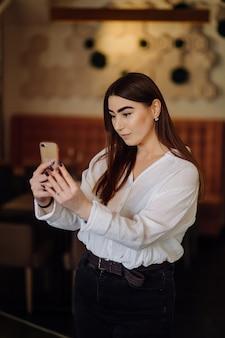 Uśmiechnięta dziewczyna spędza czas w ulicznej kawiarni przy użyciu cyfrowego gadżetu
