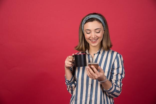 Uśmiechnięta dziewczyna sprawdzanie telefonu komórkowego z filiżanką herbaty