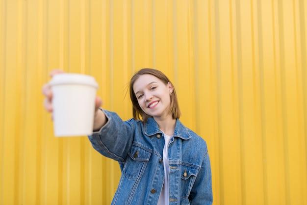 Uśmiechnięta dziewczyna stoi na żółtym tle i oferuje papierową filiżankę kawy.