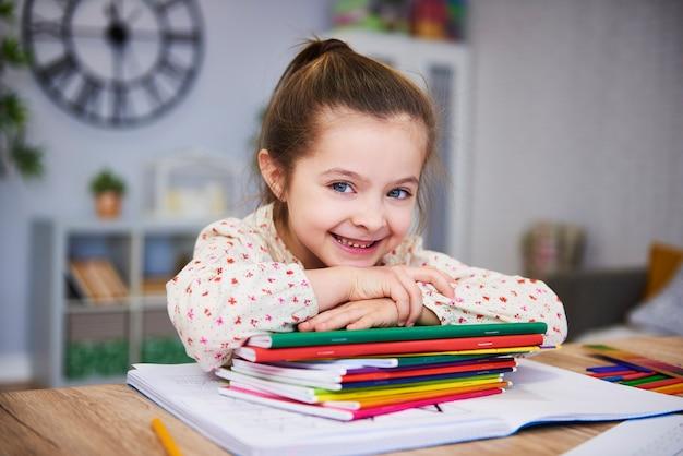 Uśmiechnięta dziewczyna studiuje w domu