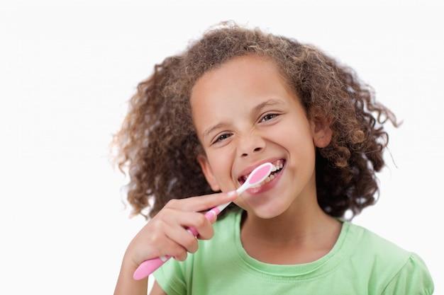 Uśmiechnięta dziewczyna szczotkuje jej zęby