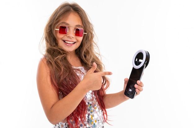 Uśmiechnięta dziewczyna trzyma czarną telefon komórkowy diodę dla selfie i wskazuje przy nim w kwadratowych czerwonych okularach przeciwsłonecznych