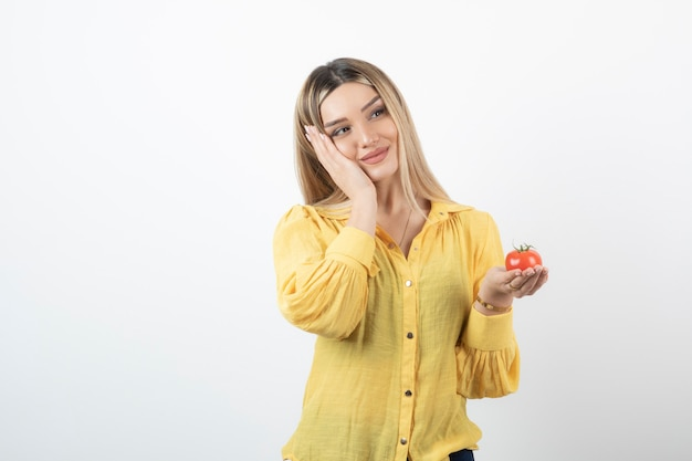 Uśmiechnięta dziewczyna trzyma czerwony pomidor i pozowanie na białym.