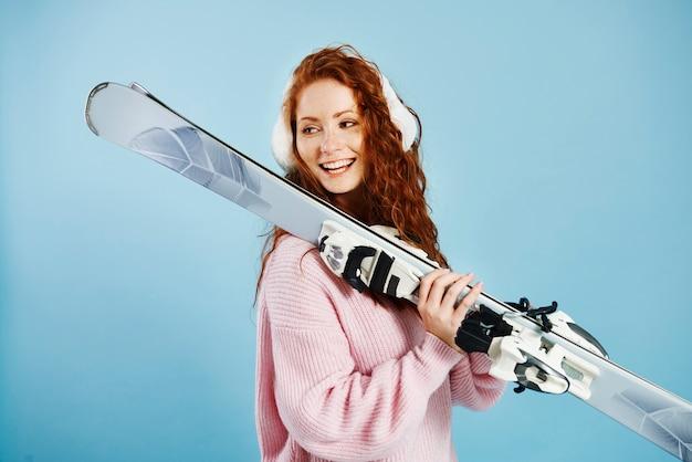 Uśmiechnięta dziewczyna trzyma jej narty