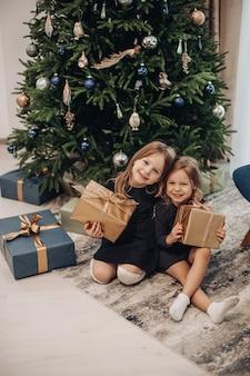 Uśmiechnięta dziewczyna trzyma prezenty świąteczne w brązowym opakowaniach prezentów