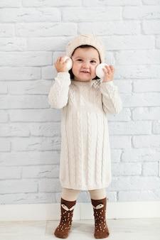Uśmiechnięta dziewczyna trzyma śnieżne piłki blisko do jej twarzy