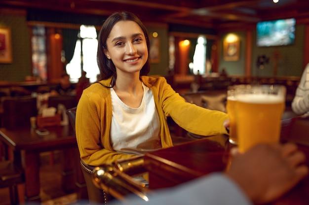 Uśmiechnięta dziewczyna trzyma szklankę piwa przy ladzie w barze. grupa ludzi wypoczywa w pubie, nocne życie, przyjaciele świętują wydarzenie w restauracji